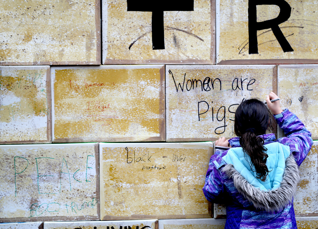 . A young girl etches a message on a wall of cardboard boxes on Pacific Avenue in Downtown Santa Cruz on Friday during an anti-Trump protest. (Kevin Johnson -- Santa Cruz Sentinel)