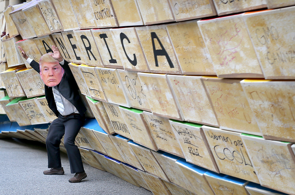 . Micah Posner, dressed as President Donald Trump, finds himself under a falling wall of cardboard boxes on Pacific Avenue in downtown Santa Cruz on Friday during an anti-Trump rally. (Kevin Johnson -- Santa Cruz Sentinel)