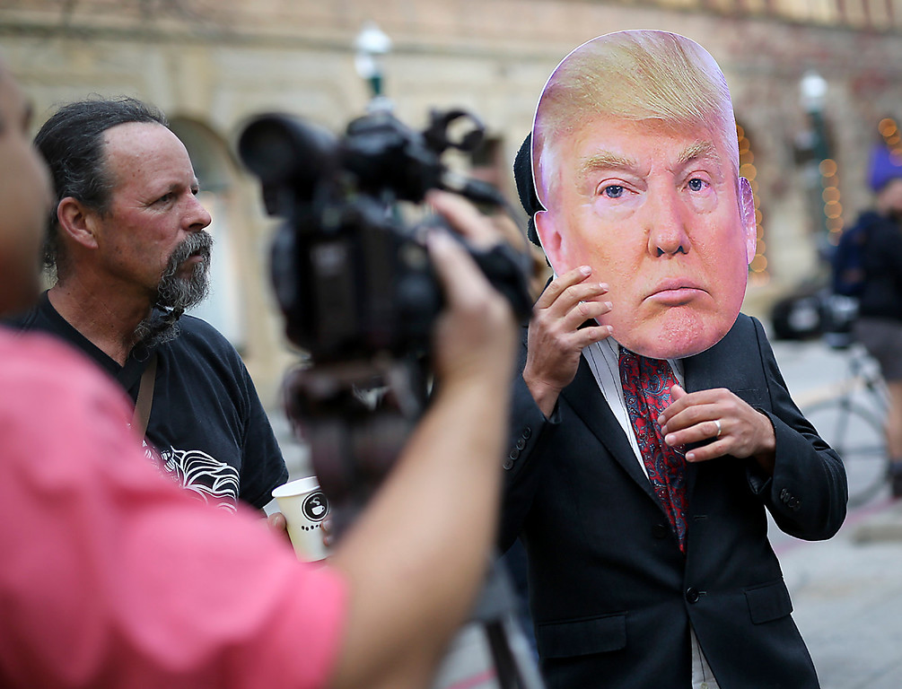 . Micah Posner speaks to the cameras on Pacific Avenue in downtown Santa Cruz on Friday while wearing an oversized Donald Trump mask. (Kevin Johnson -- Santa Cruz Sentinel)