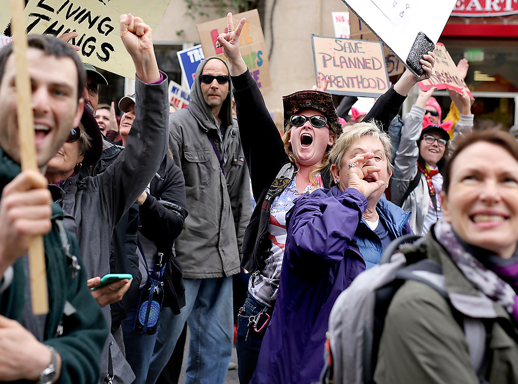 . A woman cheers amidst thousands of protestors as they march down Pacific Avenue in downtown Santa Cruz on Saturday during the Santa Cruz County Women\'s March against President Donald Trump. (Kevin Johnson -- Santa Cruz Sentinel)