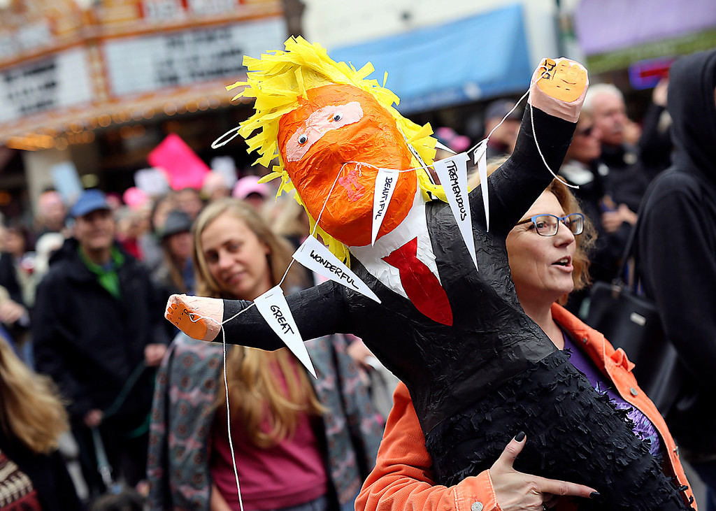 . A woman carries a Donald Trump piñata through downtown Santa Cruz on Saturday as she participates in the Santa Cruz County Women\'s March. (Kevin Johnson -- Santa Cruz Sentinel)