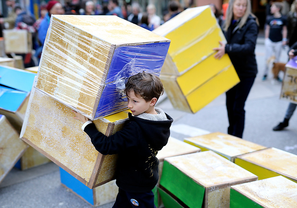 . A young boy helps clean up cardboard boxes that were used to represent blocks in Trump\'s wall in downtown Santa Cruz on Friday. (Kevin Johnson -- Santa Cruz Sentinel)