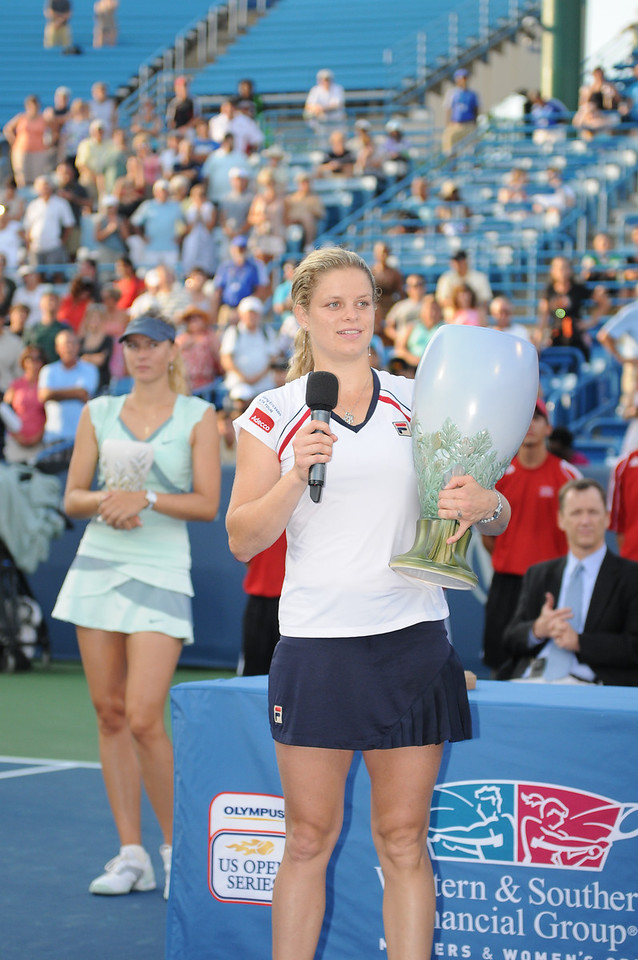 Kim Clijsters holds up the championship trophy as Maria Sharapova stands in the background in disappointment.Western & Southern Financial Group Women's Open.(CincySportsZone/Scott Davis)