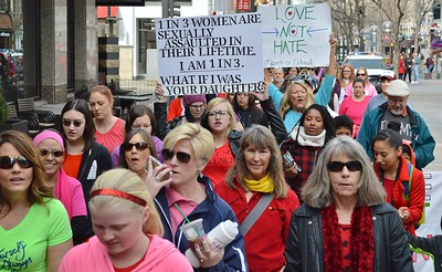 Young woman displays sign about sexual assault during 1 Billion Rising march in Denver.