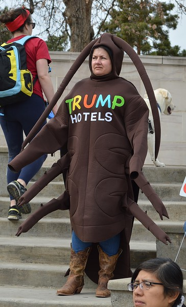 "Woman in bedbug costume with ""Trump Hotels"" on the front."