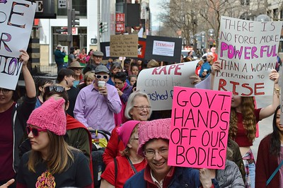 Protesters with signs at 1 Billion Rising March in Denver.