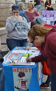 1 Billion Rising march attendee signing a petition.