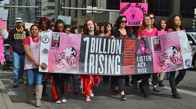 Group of women  carrying large banner at the head of the 1 Billion Risi ng march in Denver.