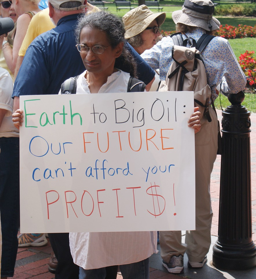 This woman protests oil company profits at a demonstration on climate change.