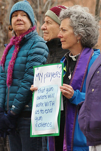 Woman clergy at gun control demonstration.