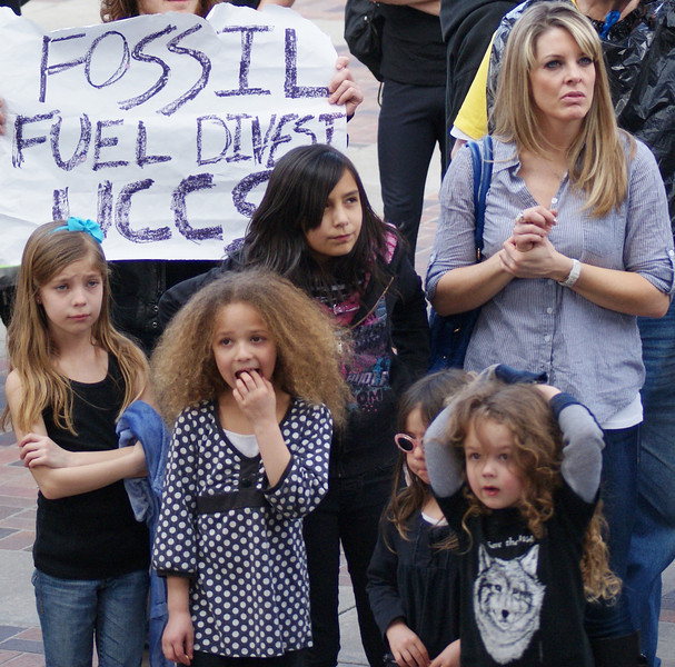 Woman with group of young children at climate change rally.