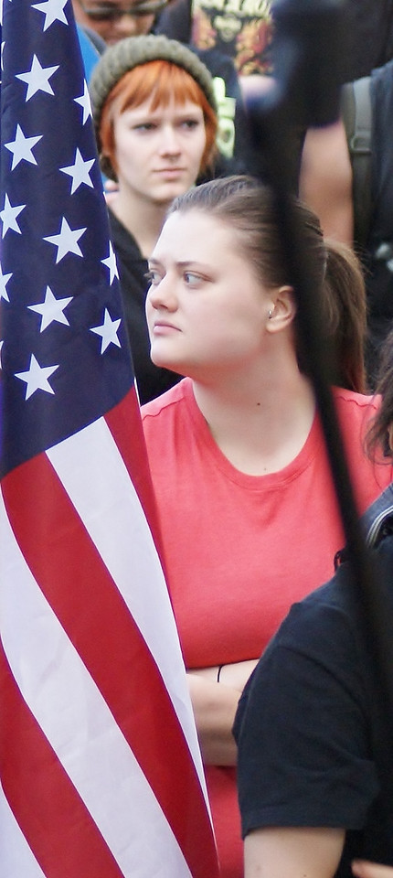 Two young women at a rally, flanked by an American flag.
