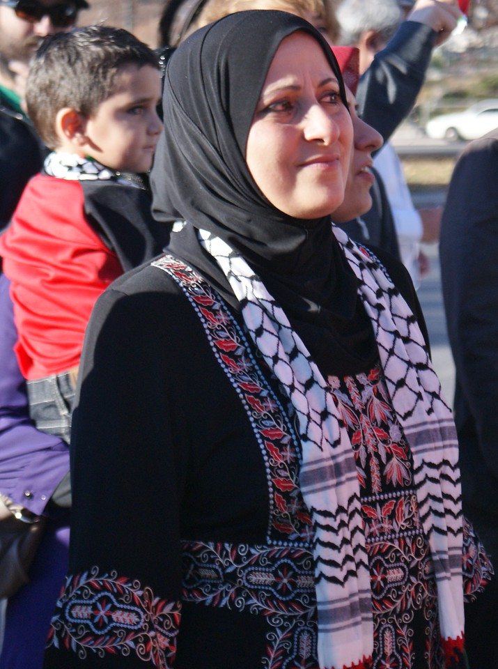 Palestinian woman in traditional dress at rally in Denver.