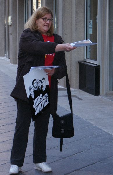This woman, a Jobs with Justice activist, passes out flyers in downtown Denver.
