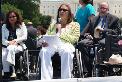 Woman in wheelchair speaks at rally for rights of disabled people.