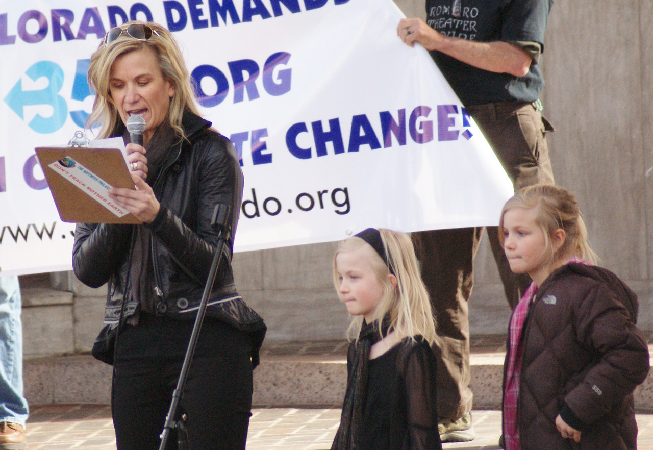 Woman with young children next to her, speaks at climate change rally.