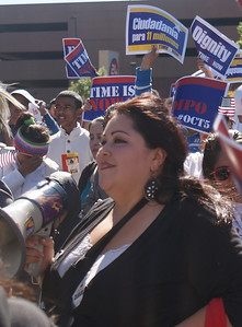 Latina woman with megaphone, people waving immigration reform signs behind her.