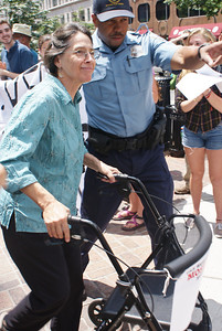 Senior woman using a walker, being arrested at an anti KXL pipeline protest in Washington,DC.