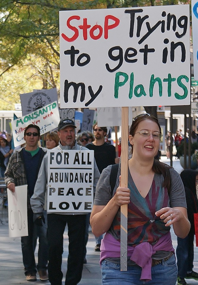 """Woman in anti GMO march with sign reading """"Stop Trying To Get Into My Plants""""."""
