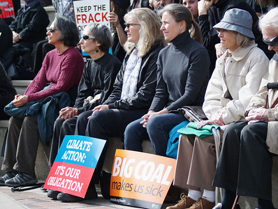 Group of women sitting at climate change rally.