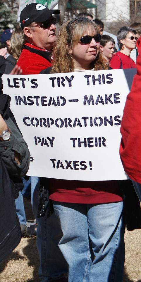 woamn at union rally calls for corporations to pay their taxes.