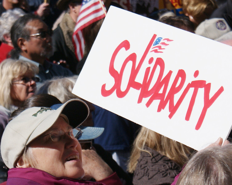 """Woman with """"Solidarity"""" sign at union rally in Denver."""