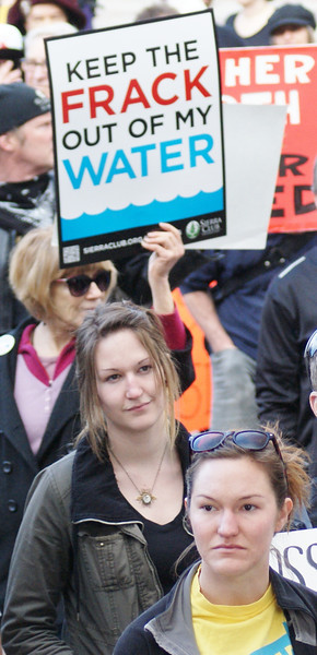 Young woman at rally, anti-fracking sign behind them.