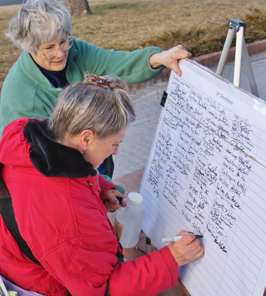 Woman signing petition against corporate personhood, at a rally in Denver.
