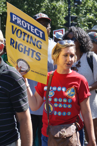 "Young woman holding ""Protect Voting Rights"" sign."