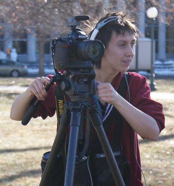 Young woman standing with camera on tripod.