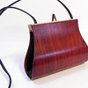 """Laelia"" wooden purse by Mark Diebolt. The purse measures 7.5"" wide x 5.5"" tall x 2.25"" deep. Made from bloodwood, curly maple, hybrid acrylic and leather and hidden magnetic clasp. $290 (price subject to change without notice). Call 800.272.3870 to order."
