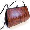 """Calliandra"" wooden purse by Mark Diebolt. The purse measures 8.75"" wide x 6"" tall x 2.75"" deep. Made from bubinga, black obechi, hybrid acrylic and leather. $305 (price subject to change without notice). Call 800.272.3870 to order."