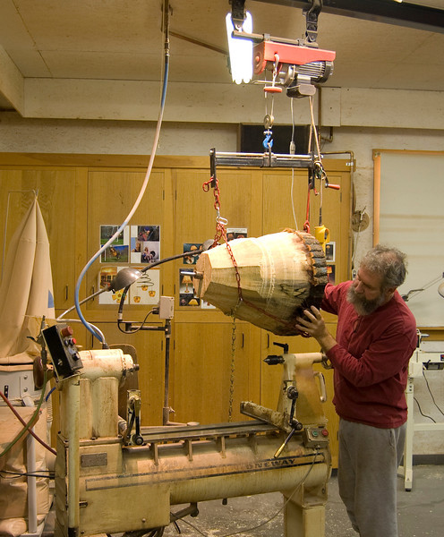 Using an electric hoist to move the heavy log piece on to the lathe