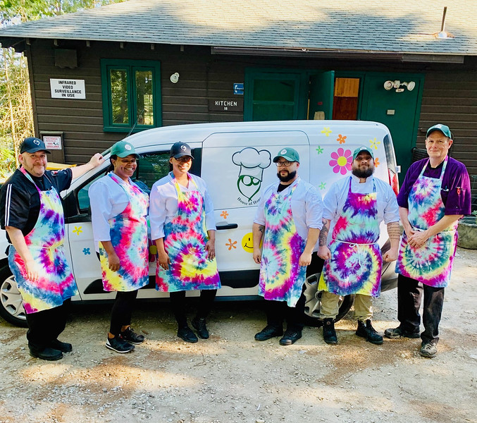 The fantastic House of Hope crew, wearing their custom, tie-dyed aprons  and standing in front of their love bus