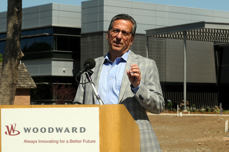 Tom Gendron, CEO of Woodward Inc., speaks during the ribbon-cutting ceremony Tuesday, June 7, 2016, for the company's new world headquarters in north Fort Collins. The new Industrial Turbomachinery Systems building behind him is part of the Fort Collins campus, as is the small brick milk house, which was part of the original Coy-Hoffman homestead. (Photo by Craig Young / Loveland Reporter-Herald)