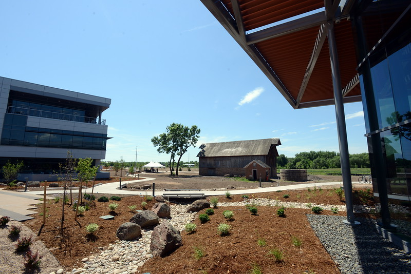 The new Woodward Inc. campus in north Fort Collins, shown Tuesday, June 7, 2016, features a 60,000-square-foot headquarters building, left, a 303,320-square-foot Industrial Turbomachinery Systems facility, right, a historic barn and milk house from the original Coy-Hoffman homestead, center, and open space along the banks of the Cache la Poudre River in the distance. (Photo by Craig Young / Loveland Reporter-Herald)