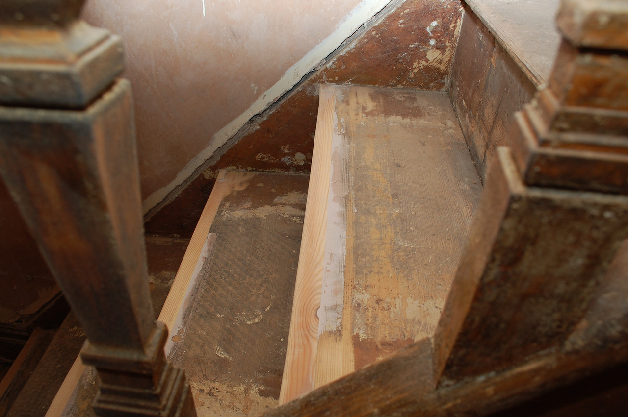 The broken staircase bullnose is repaired by cutting out the broken sections and splicing in new pieces of spruce.