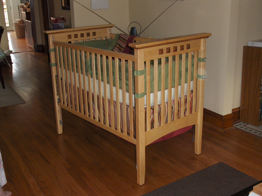 Woodworking project by Joshua Swenson.  Maple and cherry baby crib I made when expecting my first child. Plan from Rockler.  Bumper pads and crib skirt were made by my mother in law.