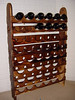 Herb Rosen (item 3) made this pine wine rack. Front shelves have scallop grooves for bottle bottoms with labels.  Rear shelves have holes for bottle necks. Shelves are secured to 4 ft supports with buttons covered screw holes.  Top coated with Minwax aerosol stain-sealer. Holds 48  wine bottles.