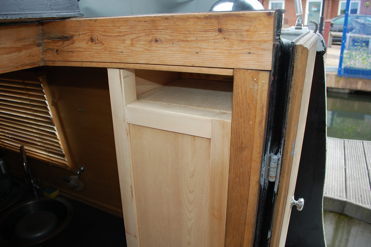 The top of the cupboard has space for key and phpne storage when driving the boat.