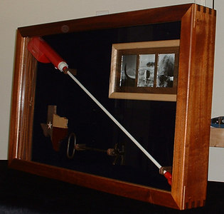 "The case is african mahogany with maple splines and a maple strip inside the frame.  The internal frame is birdseye maple with walnut-splined corners and a walnut ""mat"" framing the individual photos.  The clamps that hold the prod and brand are laminated walnut, maple, and bloodwood (satine)."