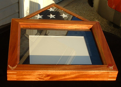 The flag in this case was flown in an F-15 during Operation Iraqi Freedom.  The case is mahogany, and the flag frame is lacewood.  The inlays and splines are maple (the inlaid silhouette of Iraq is bloodwood).  There is also a certificate that was later placed inside the frame.