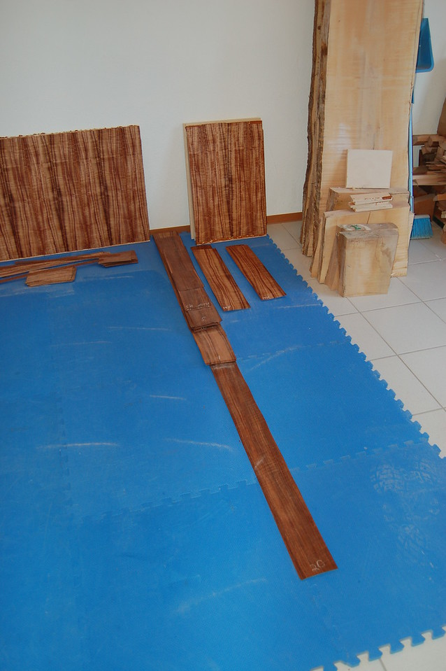 The main panels in the headboard and footboard of the bed, as well as the big panels in the nightstands and dresser are made with plywood.  I veneered the plywood with curly koa and curly etimoe (backer) veneer.  Here are some of the headboard panels with veneer on them before I cut them to size.  Also, you can see the strips of veneer I'm using.