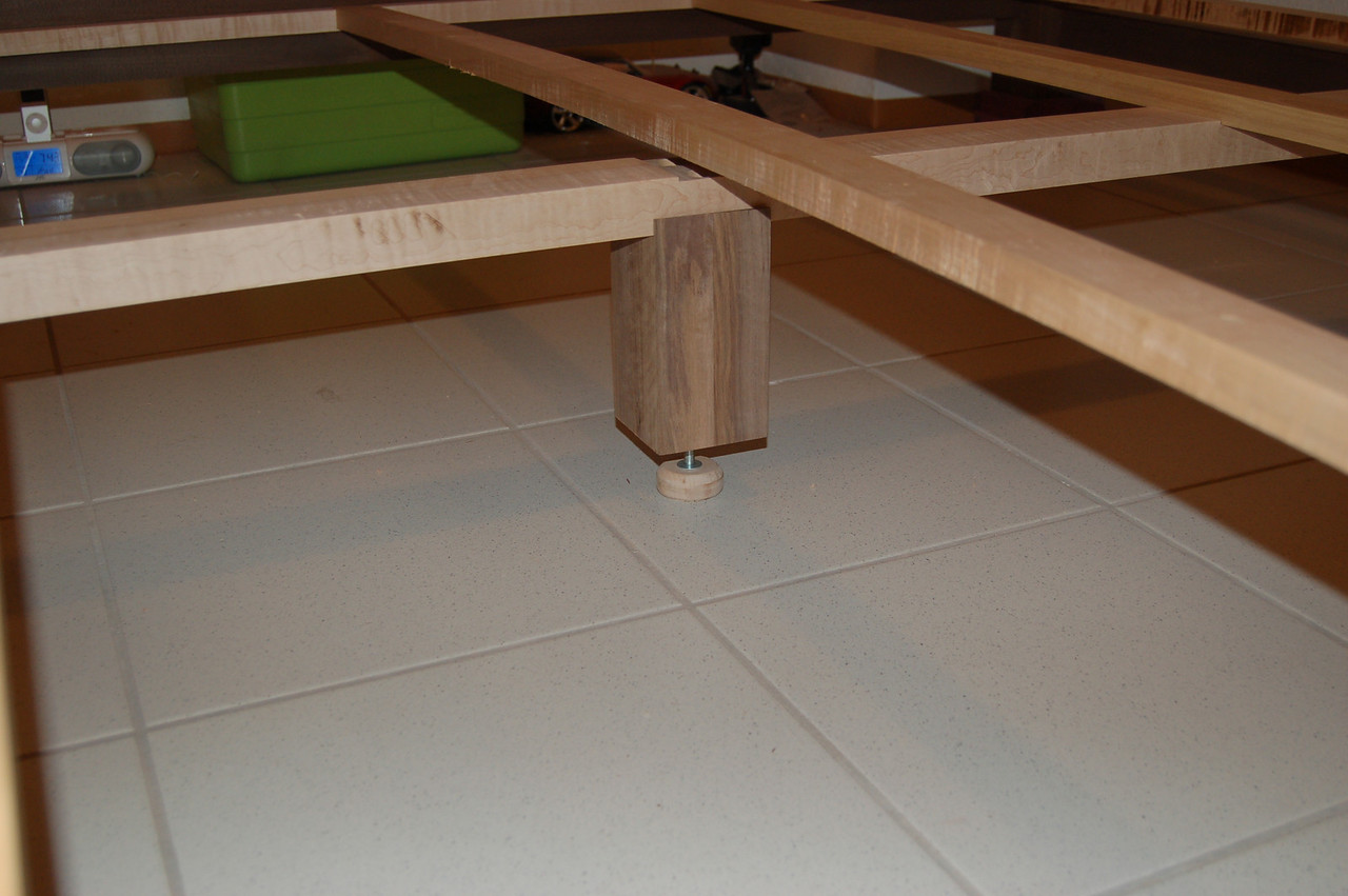 The center support post has an adjustable foot.  Also note that the cross supports are bowed upwards in the center, and come to rest in shallow grooves in the center support rail.