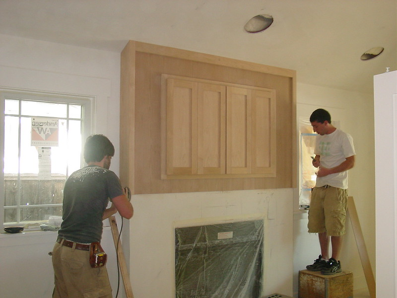 Matt and Ian working on flat screen TV cabinet over fireplace