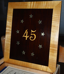 The top is hot hide glue hammer veneered with curly maple and walnut.  The inlays are curly maple and brass.  For you numerologists, note there are 9 brass stars, each with 5 points.