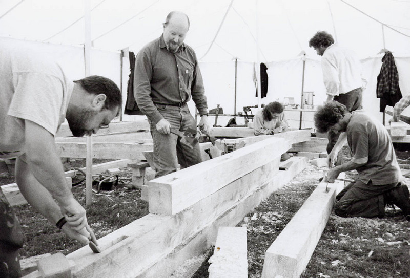 Many hands make light work. <br /> <br /> A team of people working on the handcut mortice and tenons of a post and beam frame barn.