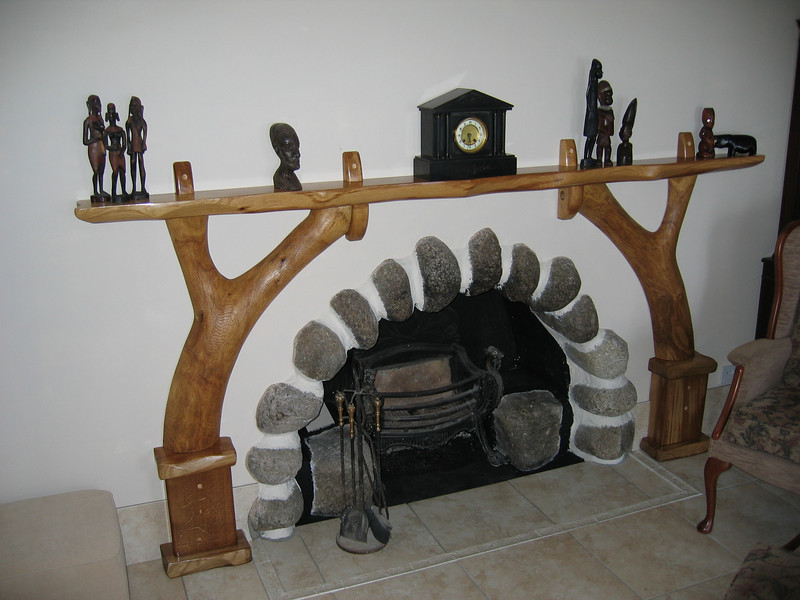 Oak mantle piece.<br /> <br /> I was asked to design and build this piece to fit with an existing fireplace in the Blackrock guest house, Corrie.<br /> Built all in local oak, the legs are both from one branch which was cut in half to form the circle shape around the stone hearth. I left the top flat for ornaments and used an oil finish for the lustre, all the other surfaces are shaped, sculpted and textured.
