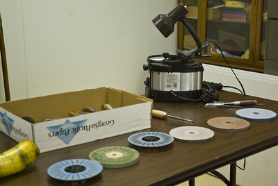 Sandpaper attached to spinning plates is used to sharpen the cutting edges.
