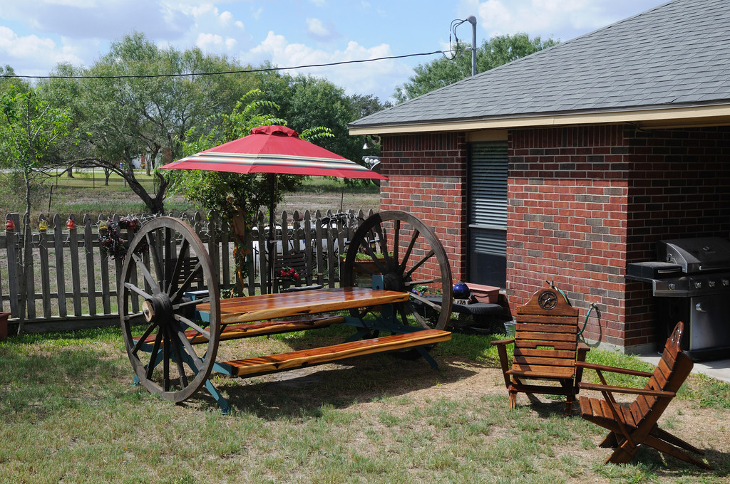 """Wagon Wheel Picnic Table.  Large wagon wheels on axles to allow table to be rolled where needed. Table top and seats are Red Cedar cut to 3 inch thickness.  Table top 36"""" X 96"""", seats 14"""" X 96"""". Legs lock, in the up and down position."""